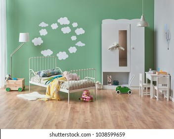 Green baby room decoration interior style cloud pattern wall and classic bed and white cupboard design with toy style brown parquet.