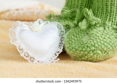 Green baby socks with a heart shape small cursion on yellow fluffy blanket