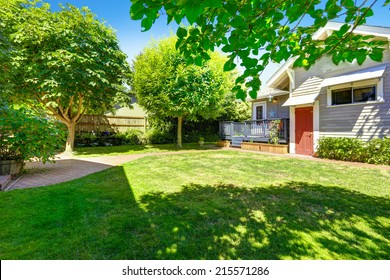 Green backayrd garden with brick tile walkway. House with wooden deck
