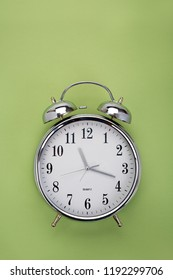 Green background and top view of a vintage analog alarm clock with place for text