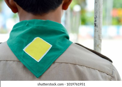 Green background and yellow frame  scout scarf with brown shirt of Thailand boy scout. Concept is learning Scout subject at school.