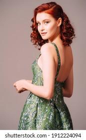 Green backless evening dress. Beautiful model wearing emerald high heels, modern feminine look for an event. Women's fashion. Adorable lady.
