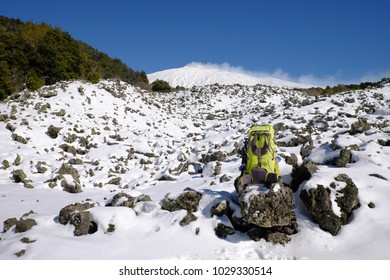 green backpack on the snow covered volcanic rock of Etna Park, Sicily
