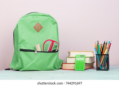 Green backpack and school supplies: notepad, books, scissors, pens, pencils, ruler, calculator is on a white wooden table on pink background