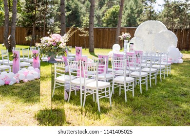 Green backyard decorated with pink balloons and flowers around chairs and wedding altar