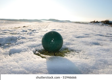 green ball on a snow covered links golf course in ireland in winter