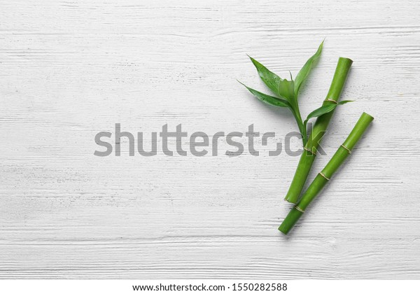 Green bamboo stems on white wooden background, top view. Space for text