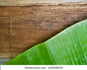 green banana leaf on wooden background, top view