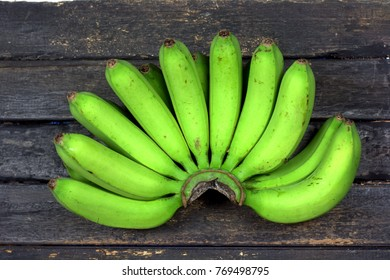Green banana or unripened banana on wooden table  top view