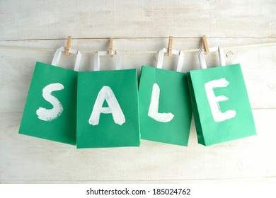 """Green """"bargain sale"""" shopping bags with clothespin."""