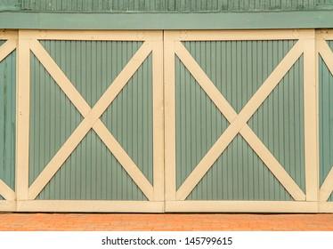 Green barn doors with cream trim and bricks