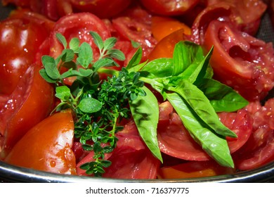Green basil, oregano and thyme with red Roma tomatoes closeup.