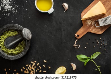 Green basil pesto - italian recipe ingredients on black chalkboard from above. Parmesan cheese, basil leaves, pine nuts, olive oil, garlic, salt, pepper and mortar. Layout with free text space.