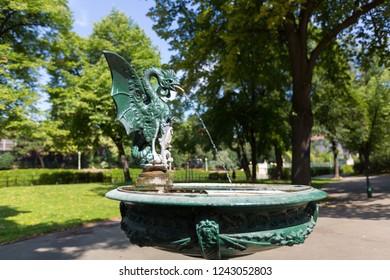 Green Basilisk Fountain spouting water in basin at Stadtpark, City Park in Vienna, Austria during summer season