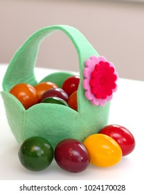 Green basket with easter colored eggs on a white background