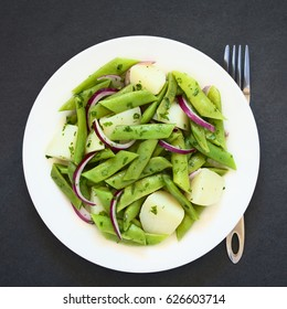 Green bean, potato and red onion salad with parsley, photographed overhead on slate with natural light