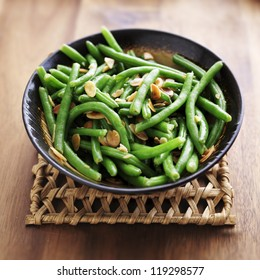 Green beans with almonds in wooden bowl