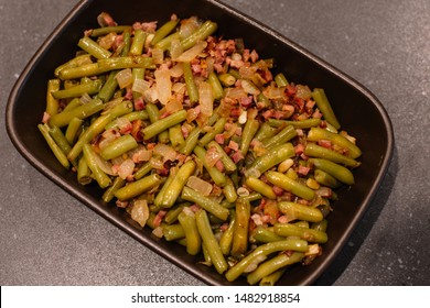 Green beans with ham. Plate of green beans cooked with serrano ham on a pyrex