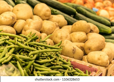 Green Beans, Irish Potatoes, Cucumbers, Onions on display for sale at a Farmer's Market