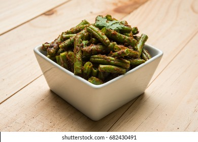 Green beans Masala dry curry, Indian vegetable recipe served in square bowl over colourful background, selective focus