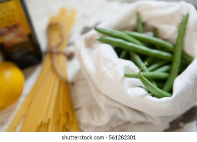 Green beans sit next to spaghetti and olive oil,