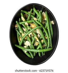 Green beans with toasted almonds, in black bowl. Isolated on white, top view.