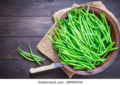 Green beans top view on rustic wood background text space.