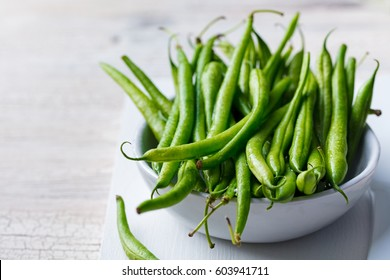 Green beans in white bowl on cutting board.