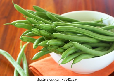 Green beans in a white bowl on orange napkin