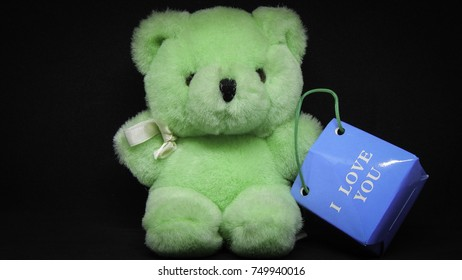 "Green bear toy with blue shopping bag with ""i love you"" label on black background"