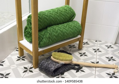 Green beautifully folded towels on a white shelf with a massage brush and washcloth.