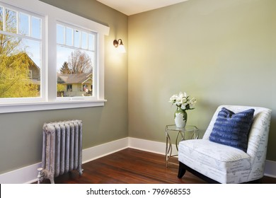 Green bedroom nook with an armless chair with blue pillow and a small glass table. Northwest, USA