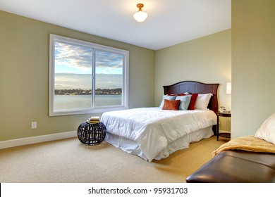 Green green bedroom with water view and white bedding.