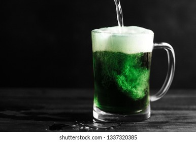 Green beer being poured in a clear glass mug