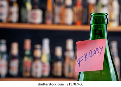 Green beer bottle in a bar with a note Friday.