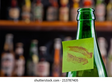 Green beer bottle with a kissed note