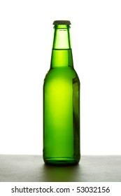 Green beer bottle over white background illuminated from the back