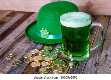 Green beer with fun decoration on wooden background.