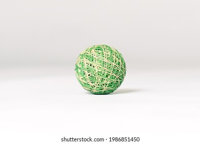 Green and beige knitted ball, pet toy, lying down on emtpy white background in the center of composition. Copy space.