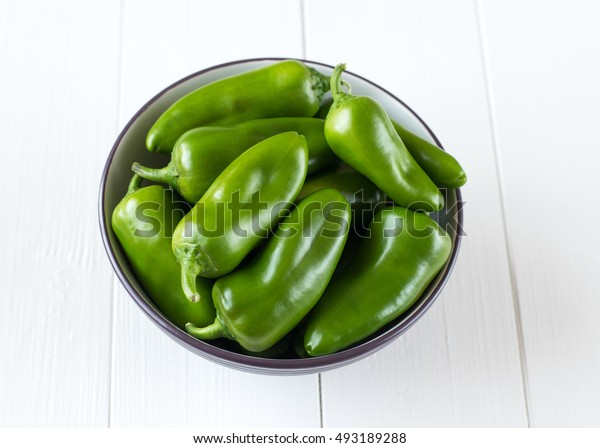 Green bell pepper in a bowl on a wooden table. Healthy food concept.