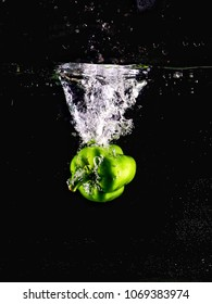 Green bell pepper drop in clear water drops isolated on black background with bubble and water splash