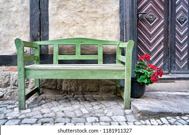 green bench in front of a half-timbered house in the old town of Quedlinburg in Germany