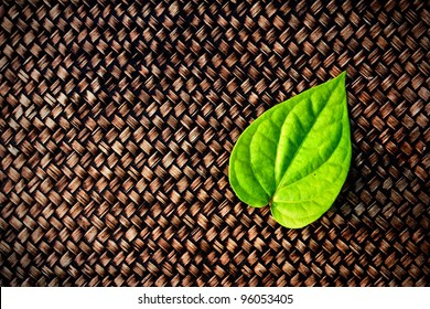 a green betel leaf on brown woven  texture background