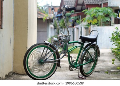 Green bicycle on a street. This bike is also known as the lowrider.
