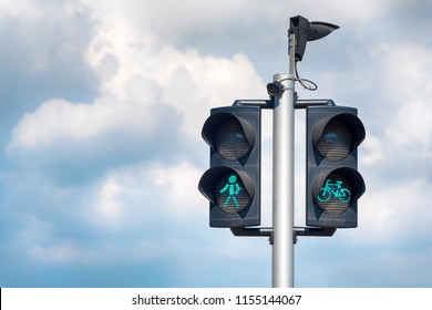 Green bicycle and pedestrian traffic lights. Green traffic light for bikes, gives cyclists priority, pedestrians crossing traffic lights with city background.