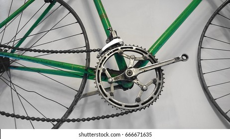 green Bicycle that big wheel hanging on stone background. vintage abandoned Bicycle hanged on gray wall. chain with pedals. hipster interior