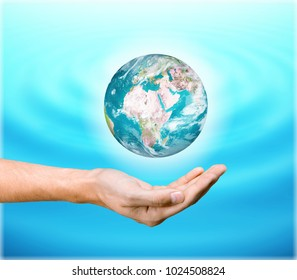 Green big earth among women hands on turquoise blue water background: World ocean & environment protection day concept: Saving CSR BIO healthy earth planet: Element of the image furnished by NASA