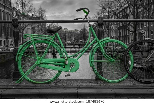 Зеленый велосипед изолирован на черно-белом через канал Амстердама. Очень капризное небо на заднем плане.