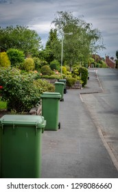 Green bin day on a quiet street with green wheelie bins lined up on the footpath.