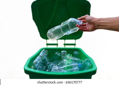 Green Bin are full with clear plastic bottles inside and a hand dropping a plastic bottle to bin on white background in recycle concept, garbage, waste,trash,reuse,save the earth,isolated,throw away